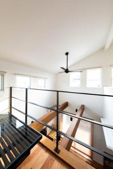 上下階のリビングをつなぐ吹き抜けのあるインダストリアル調デザインの写真
